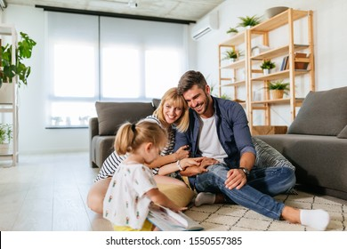Parents playing with daughter during family time at home