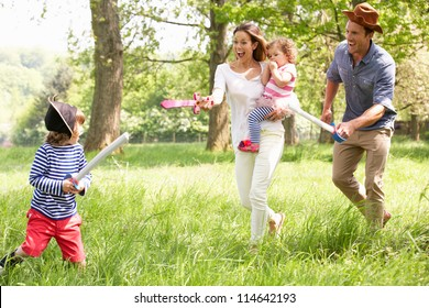 Parents Playing Exciting Adventure Game With Children In Summer Field