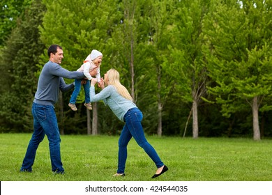 Parents playing exciting  with child In the park.Happy family.