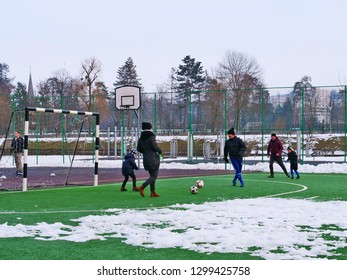 Parents are playing football (soccer) with their children on the playground in winter in Cluj-Napoca, Romania - January 19, 2019