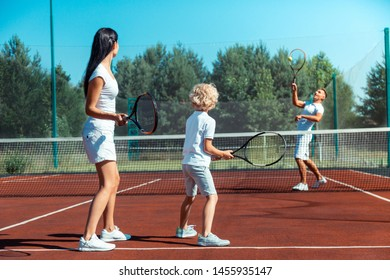 Parents playing tennis. Loving parents playing tennis with their cute blonde-haired son outside on summer day