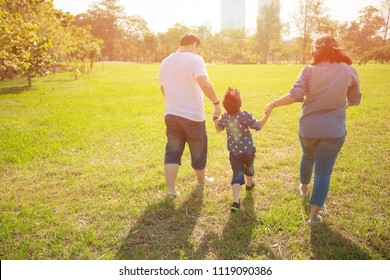 Parents playing with their  child in the field. Happy family life style concept.