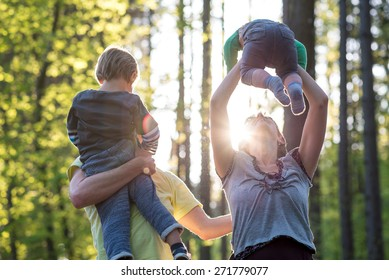 Parents playing with their two young children outdoors in a green spring forest backlit by a glowing sun as they enjoy the tranquility of nature.
