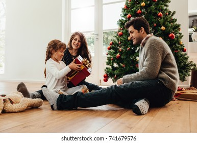 Parents presenting gift to their daughter sitting beside a Christmas tree. Little girl looks happy holding her Christmas gift.