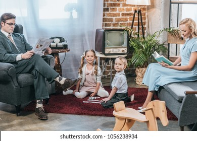 parents reading book and newspaper while kids playing with dominoes and smiling at camera, retro style