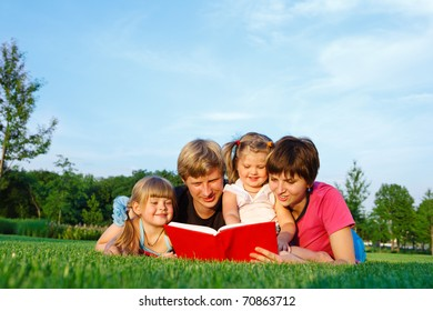 Parents reading a book to their daughters