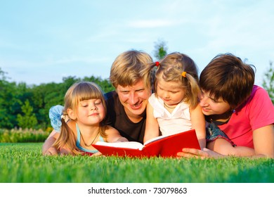 Parents reading book to their sweet offsprings