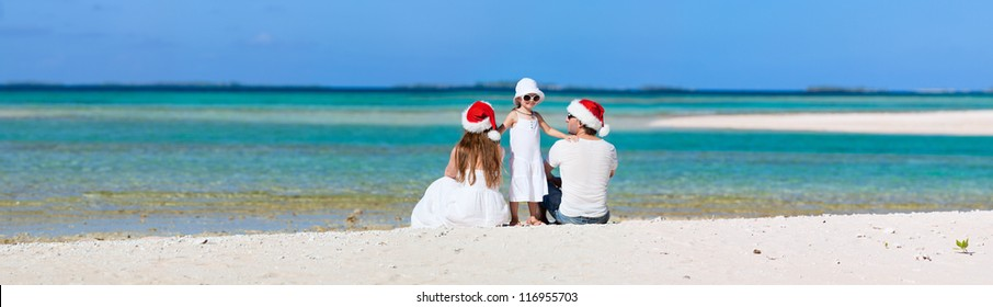 Parents in Santa hats and their little daughter on a tropical beach