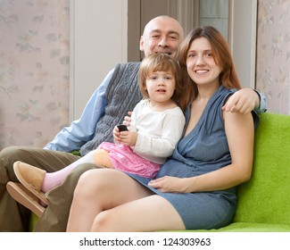 Parents sits on sofa with their child while looking at the camera