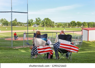 Parents sitting in folding chairs watching a high school baseball game