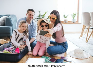Parents with small daughters indoors at home, packing for summer holiday.