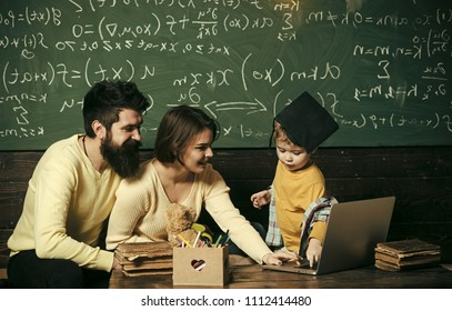 Parents teaches son, chalkboard on background. Modern education concept. Smart child in graduate cap likes to study. Parents teaching kid to use laptop. Boy presenting his knowledge to mom and dad.