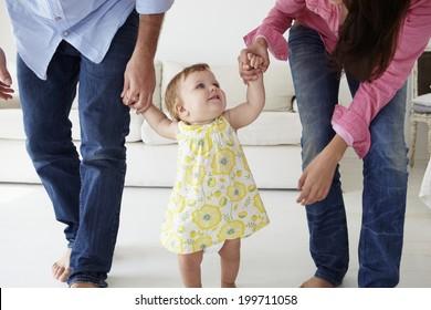 Parents teaching baby girl to walk