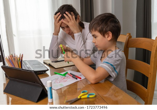 Eltern unterrichten Kinder zu Hause, Schulbildung zu Hause, Mutter hilft ihrem Sohn, Hausaufgaben zu machen