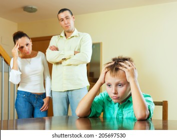 Parents and teen son after quarrel at home. Focus on boy