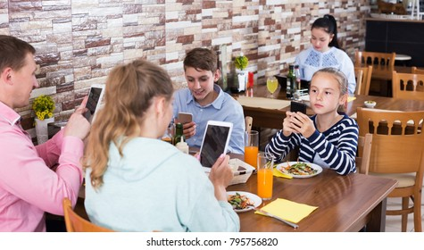 Parents with teenage children having dinner in cafe and phubbing