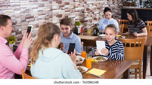 Parents with teenage kids having dinner in family cafe and phubbing
