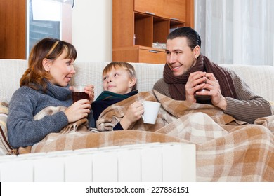 parents and teenage son warming near warm heater in home