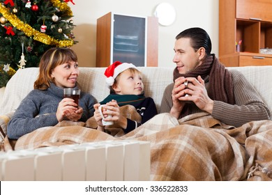 parents and teenage son warming near warm heater in Christmas time