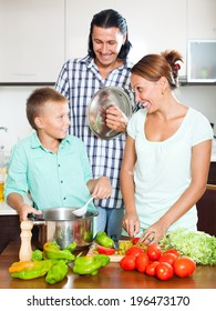 Parents and teenager cooking together at home kitchen