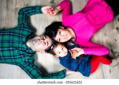 Parents with their 18 months old daughter, studio shot.