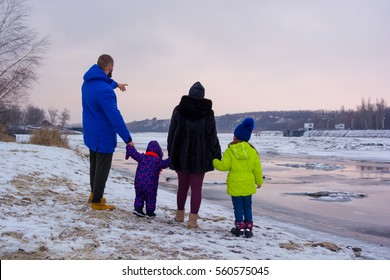 Parents with their children are watching into the distance and staying on the bank of long river