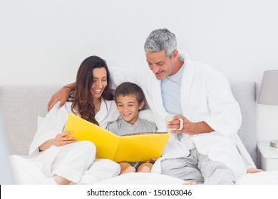 Parents with their son on bed looking together at photograph album at home