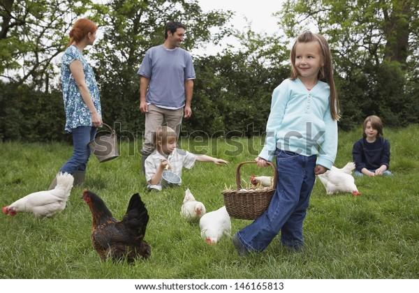 Parents with three children feeding hens on grassland