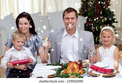 Parents toasting with champagne in Christmas dinner against snow falling