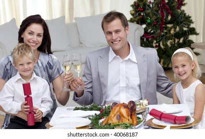 Parents toasting with wine in Christmas dinner at home