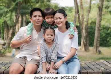 Parents and twins boy and girl sitting on wooden bridge in a park
