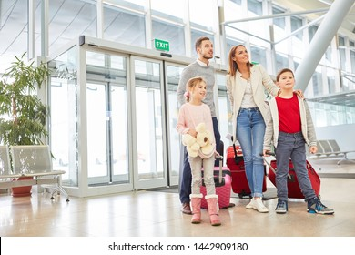 Parents and two children with luggage in the airport terminal are looking forward to a family vacation