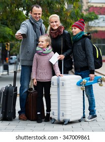 Parents with two kids and baggage taking selfie on smartphone