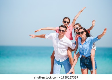Parents with two kids have fun on the beach