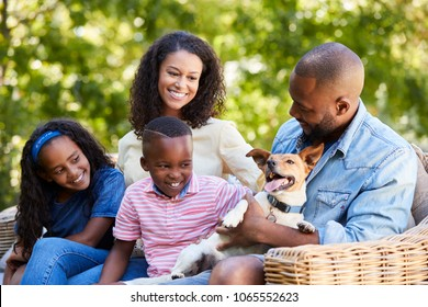 Parents and two kids sitting with pet dog in the garden