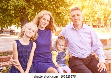 Parents with two little daughters at park. Happy family portrait. Nature lifestyle. Summer time. Caucasian people together. Outdoor parenthood