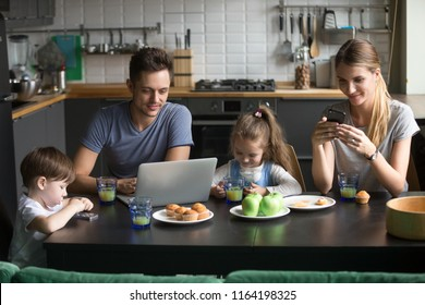 Parents using laptop and smartphones having breakfast with children, smiling dad reading morning online computer news while mom and kids entertaining with phones apps, family gadget addiction concept