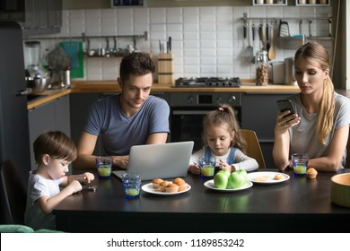 Parents using laptop and smartphones having breakfast with children, bored father writing email, searching internet while mother, son and daughter using phone apps, ignore, family gadget addiction