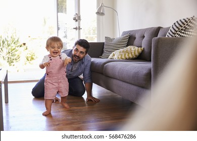 Parents Watching Baby Daughter Take First Steps At Home