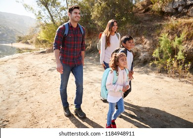 Parents and young children on a mountain hike in sunshine