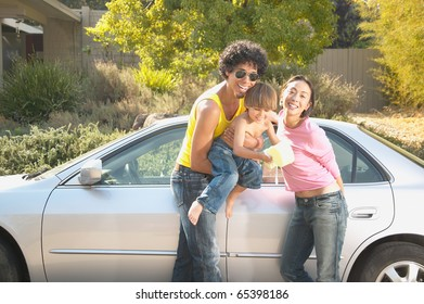 Parents and young son washing car