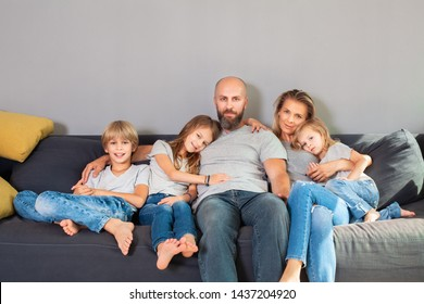 Parents,teenage son and two cute daughters sit on the sofa and spend time together.Close up of young happy loving family hugging while sitting on the sofa in living room, happy lifestyle family