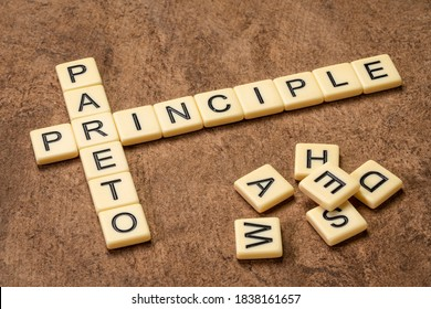 Pareto principle crossword in ivory letters against textured handmade bark paper, business, productivity, resource allocation and priorities concept