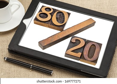 Pareto principle or eighty-twenty rule represented in wood letterpress printing blocks on a digital tablet screen