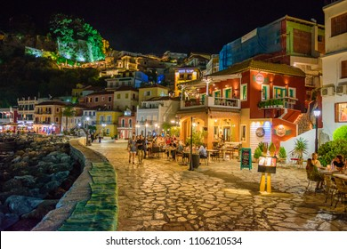 PARGA, GREECE - MAY 2018: The amazing coastal city of Parga at night. Tourists and visitors walk across the coast next to the beautiful decorated shops, and restaurants. Parga, Epirus, Greece, Europe.