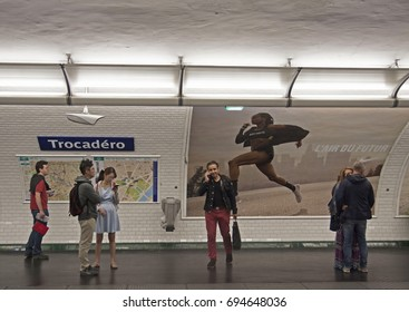 PARIJS , FRANKRIJK - JULY 23 ,2017: Waiting travelers on a metro station in Paris. With orange chairs and a big billboard on the wall on july 23 ,2017 in Paris,France