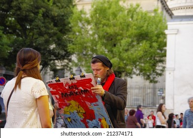 PARIS -  1 JULY 2014: Painter and his model on Montmartre hill on 1 JULY 2014 in Paris, France. Many artists worked of Montmartre such as Pablo Picasso or Vincent van Gogh