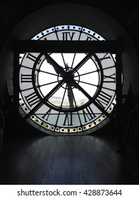 PARIS - 26 JUNE 2015: On the top floor of the Musee d'Orsay looking out of the clock onto the city of Paris. Silhouette of clock, backlit clock in former train station.