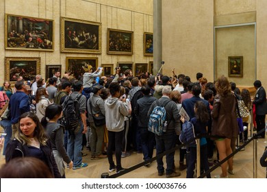 PARIS - APRIL 2, 2018: Crowd of the unidentified people take pictures of the Mona Lisa in Louvre,  portrait painting by  Leonardo da Vinci  in Paris, France