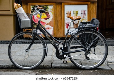 PARIS - APRIL 24, 2016: Fresh french breads, baguettes in a basket on a bicycle